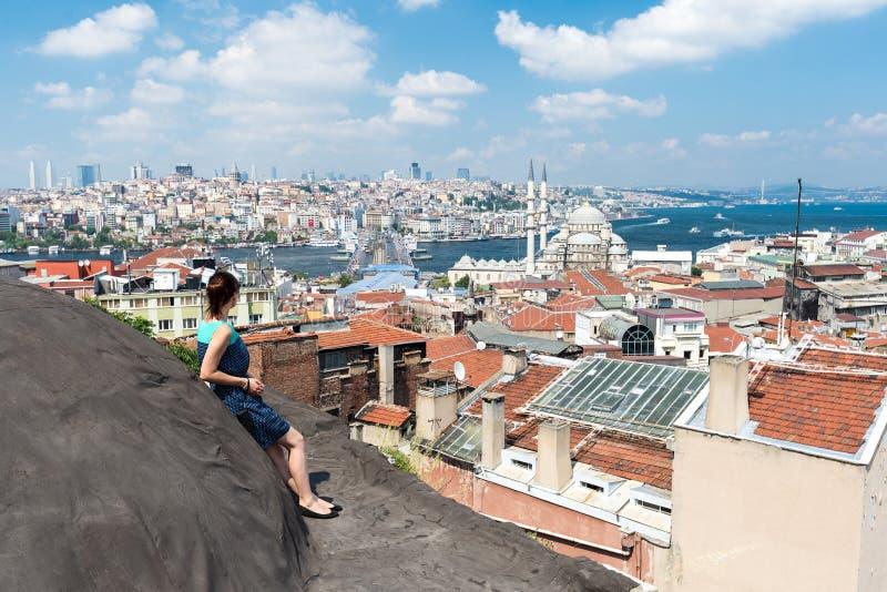 Menina que está no telhado e que olha a cidade Istambul imagem de stock royalty free