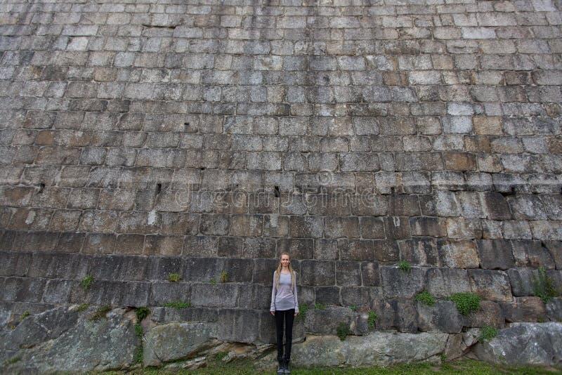 Menina que está perto de uma parede de pedra enorme porto fotos de stock