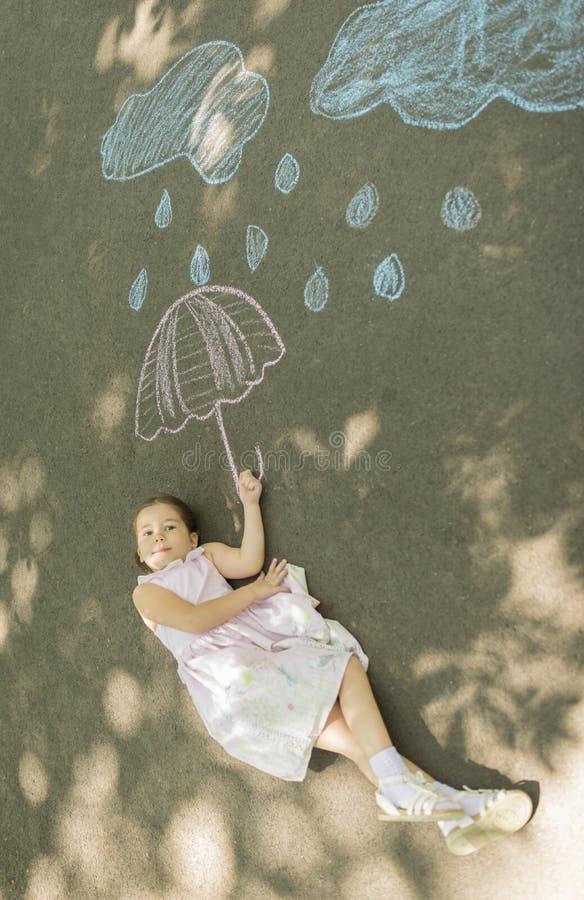 A menina que estabelece no asfalto após a tiragem nubla-se com gotas e guarda-chuva da chuva com giz fotos de stock royalty free