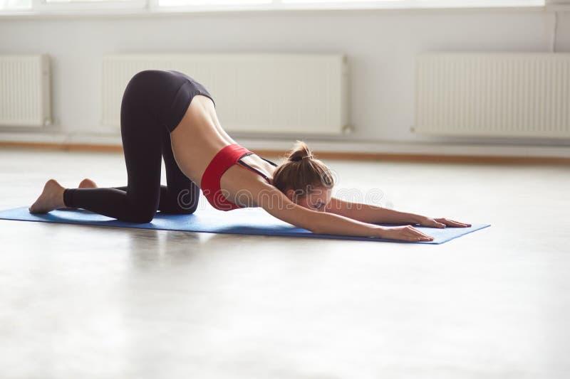 A menina que estica e que faz pilates exercita na esteira azul fotos de stock royalty free