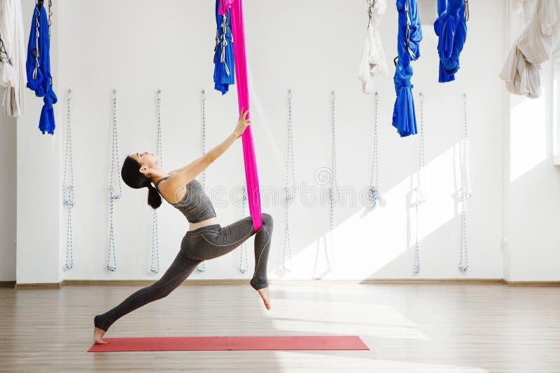 Menina que estica os pés com ajuda da rede Ioga aérea do exercício imagens de stock royalty free