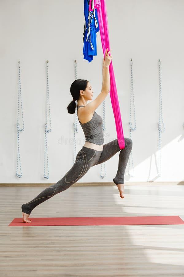 Menina que estica os pés com ajuda da rede Ioga aérea do exercício fotos de stock