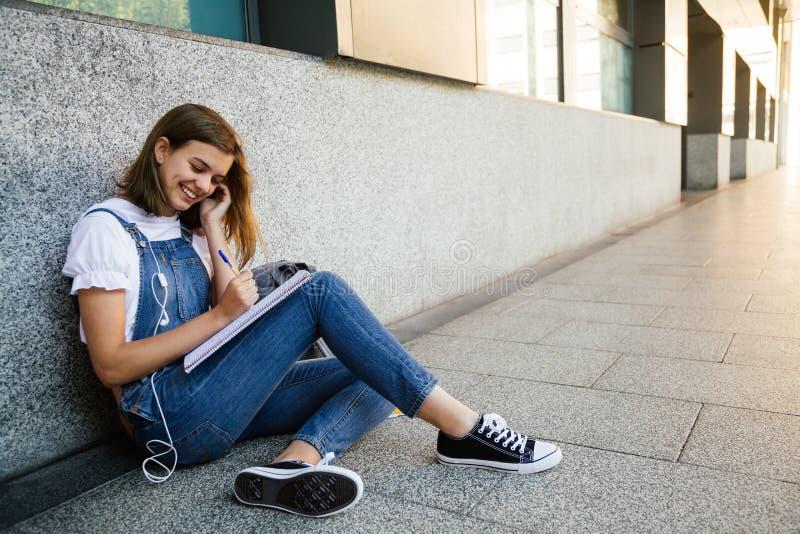 Menina que estuda com a música que senta-se no assoalho fotografia de stock royalty free