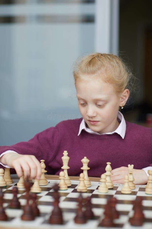 Menina que estuda figuras da xadrez foto de stock royalty free