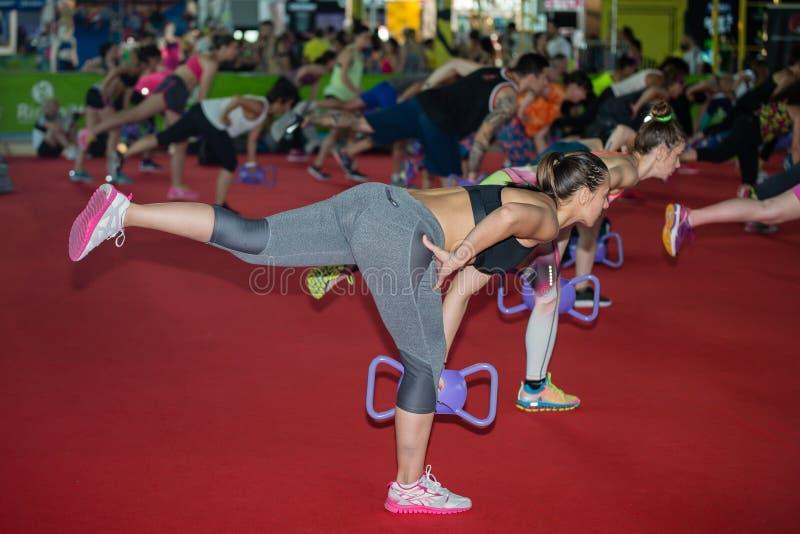 Menina que exercita com peso do Gym na classe da aptidão no Gym fotografia de stock royalty free