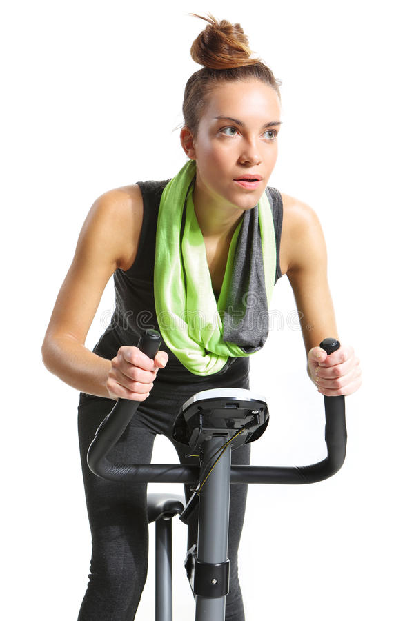 Menina que exercita na bicicleta de exercício imagens de stock
