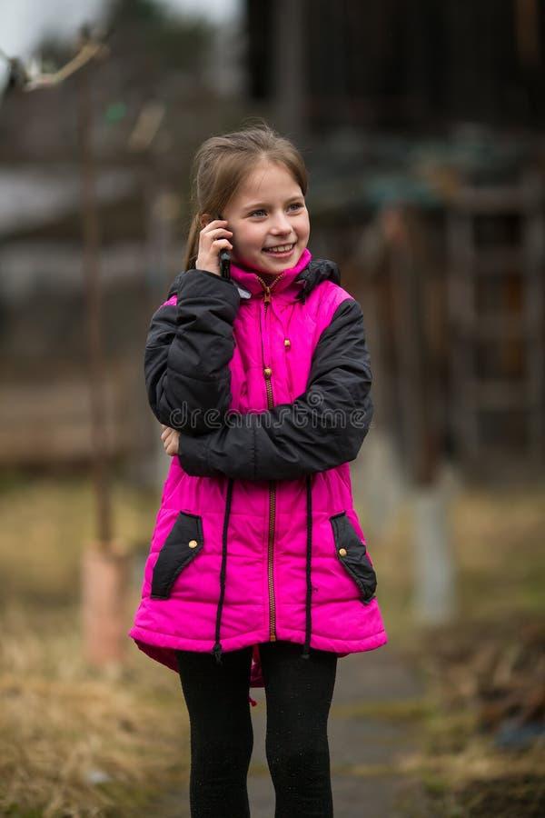 Menina que fala na posição móvel na rua imagens de stock royalty free