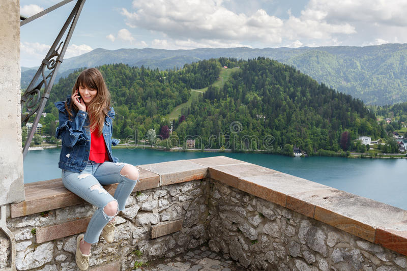 Menina que fala no telefone da parte superior do castelo da montanha com opinião do vale e no lago no fundo Copie o espaço fotografia de stock royalty free