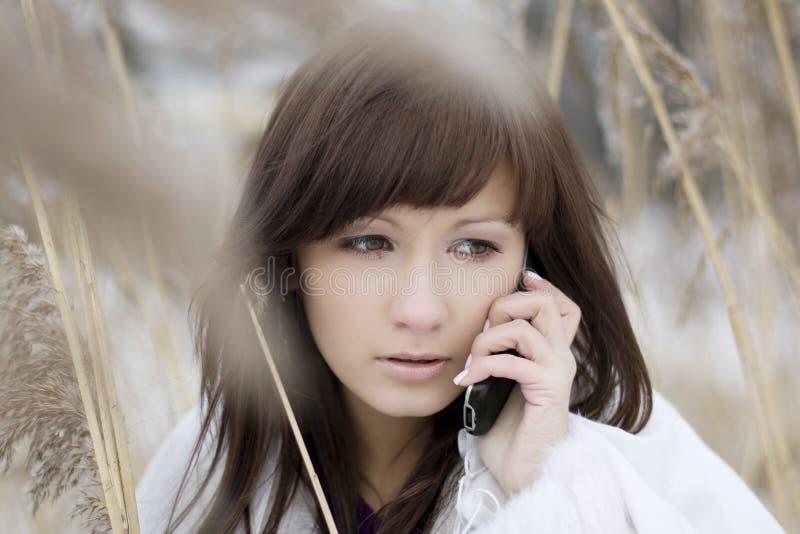 Menina que fala no telefone na lingüeta foto de stock