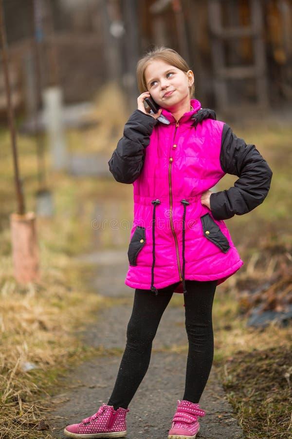 Menina que fala no telefone que está na rua foto de stock royalty free
