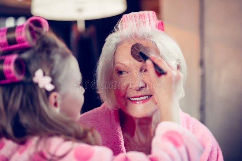 Menina que faz a composição para sua avó que põe algum pó de cara sobre fotografia de stock royalty free