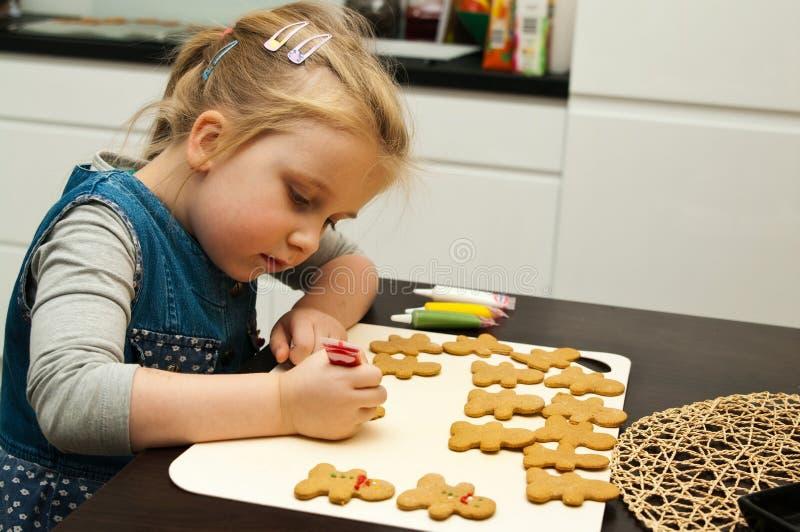 Menina que faz cookies do pão-de-espécie para o Natal imagem de stock