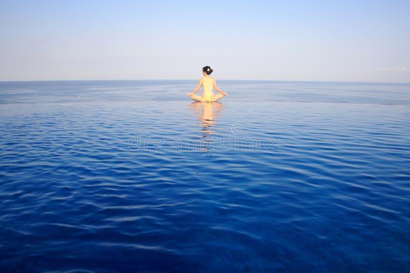 Menina que faz a ioga com opinião do mar