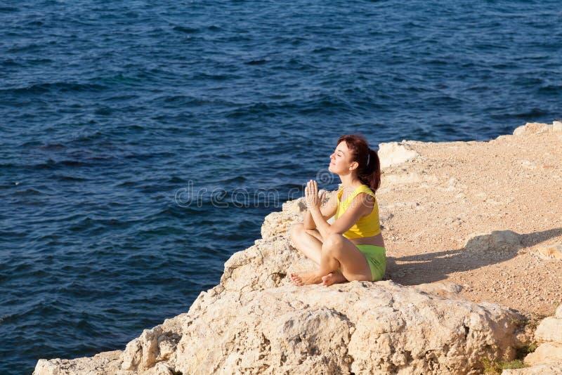 Menina que faz a ioga na praia pelo mar fotografia de stock