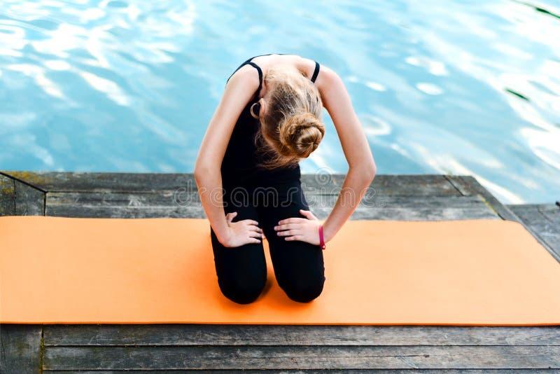 Menina que faz a ioga no banco de rio a criança é contratada nos pilates em um tapete alaranjado perto do lago imagens de stock