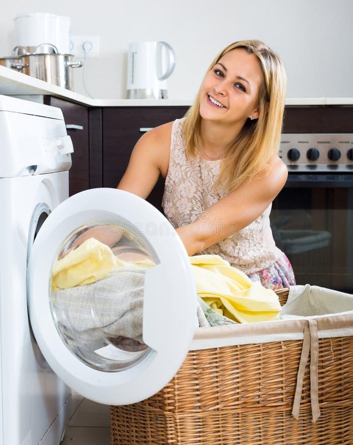 Menina que faz a lavanderia em casa foto de stock