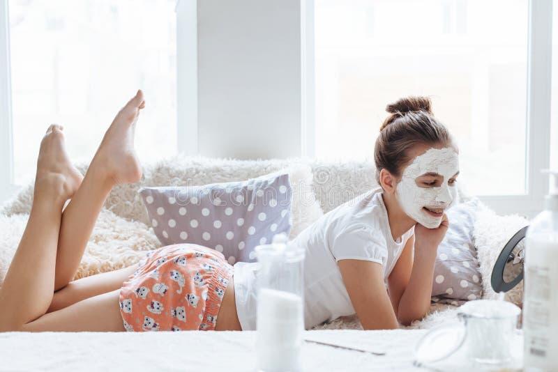 Menina que faz a máscara do facial da argila imagens de stock