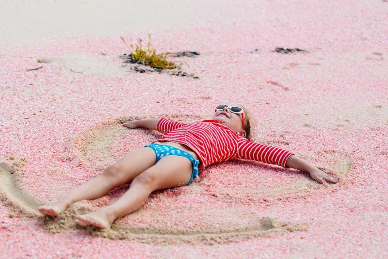 Menina que faz o anjo da areia imagens de stock royalty free