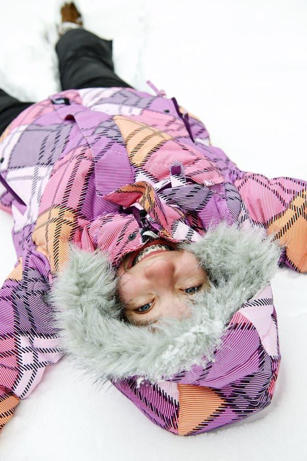 Menina que faz o anjo da neve foto de stock