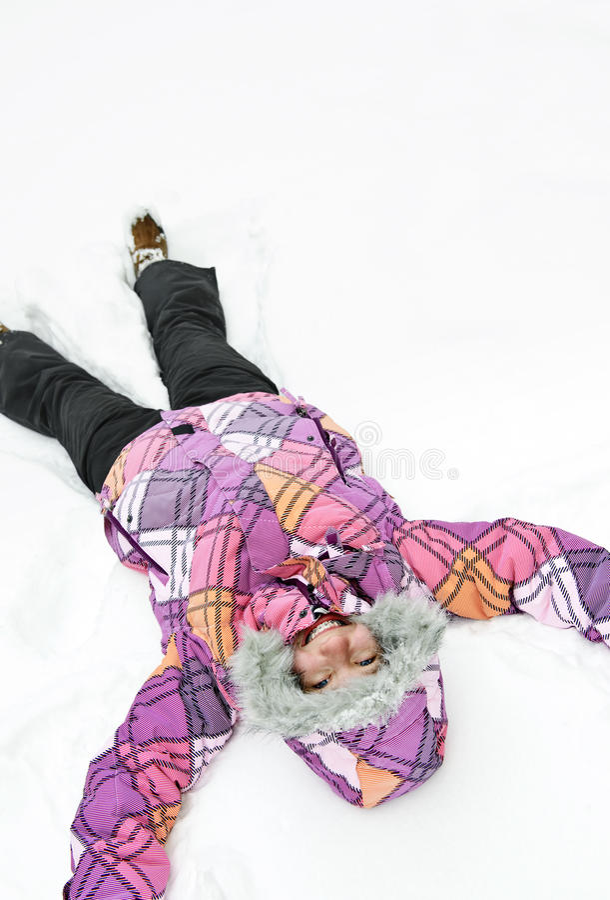 Menina que faz o anjo da neve imagens de stock royalty free