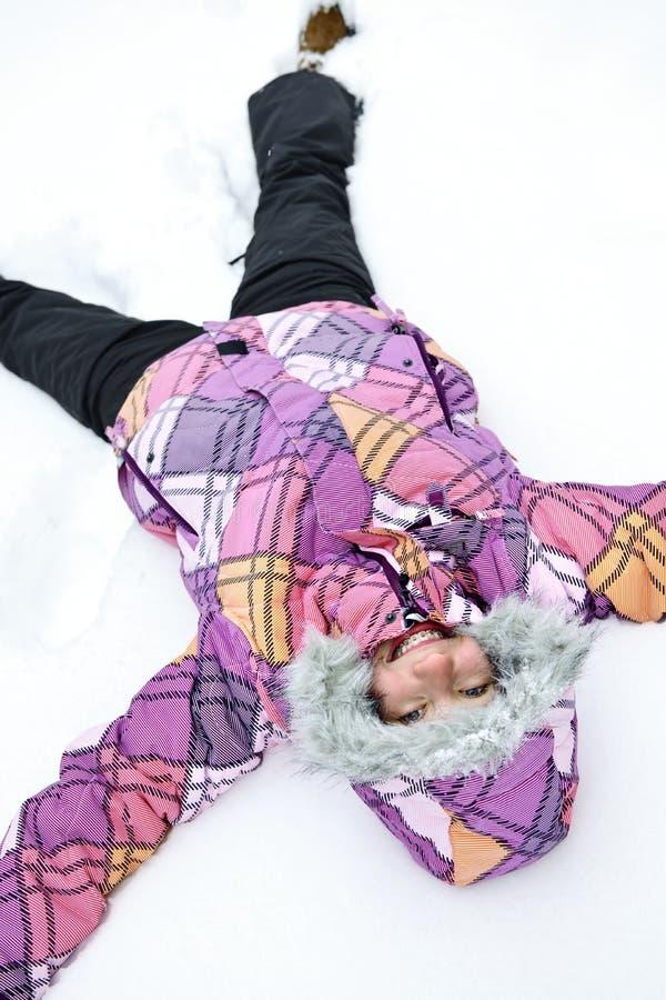 Menina que faz o anjo da neve imagens de stock