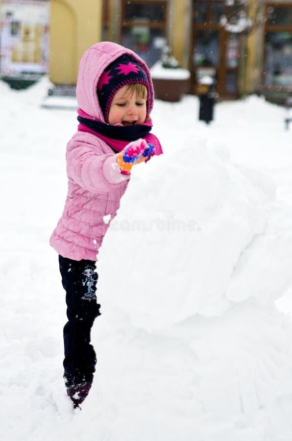 Menina que faz o boneco de neve imagem de stock