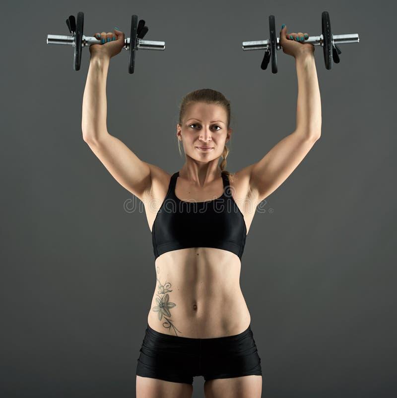 Menina que faz o exercício do ombro com pesos imagem de stock
