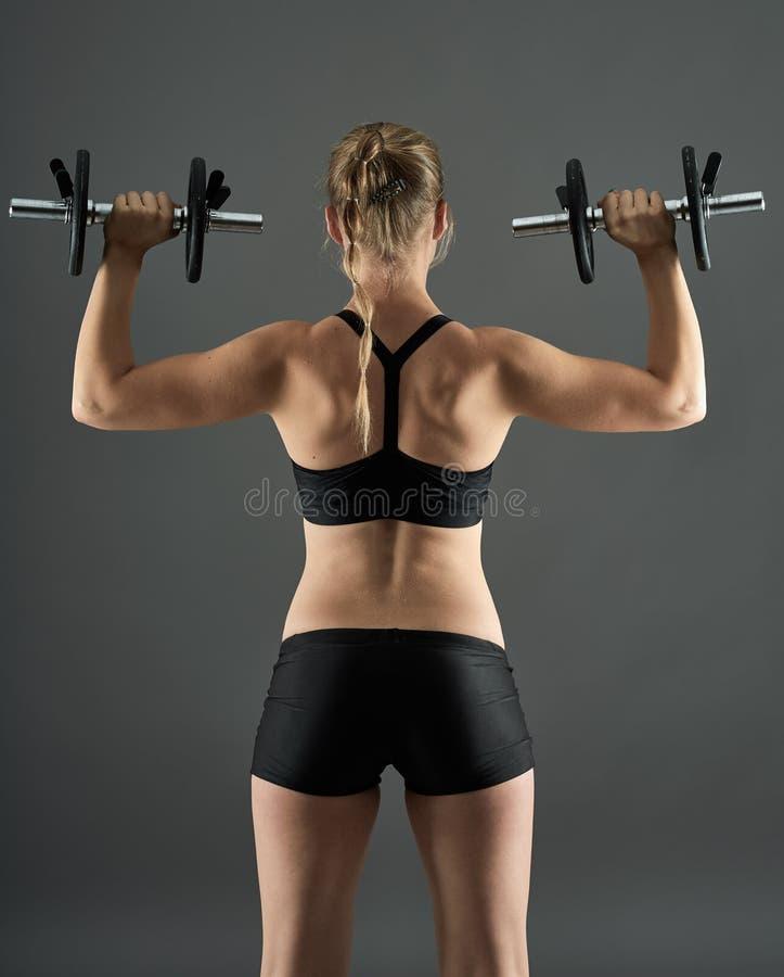 Menina que faz o exercício do ombro com pesos fotografia de stock