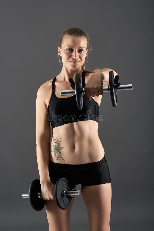 Menina que faz o exercício do ombro com pesos imagem de stock royalty free