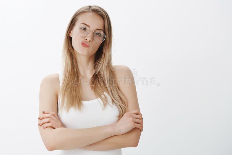 A menina que faz o julgamento que está hesitante, smirking, cruzamento de pensamento cede o corpo e cabeça da inclinação como a o fotos de stock