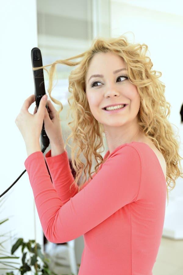 Menina que faz o penteado com ferro liso foto de stock