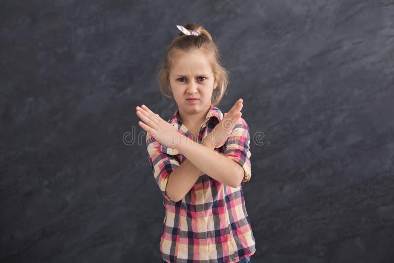 Menina que faz o sinal da parada com mãos cruzadas fotografia de stock royalty free