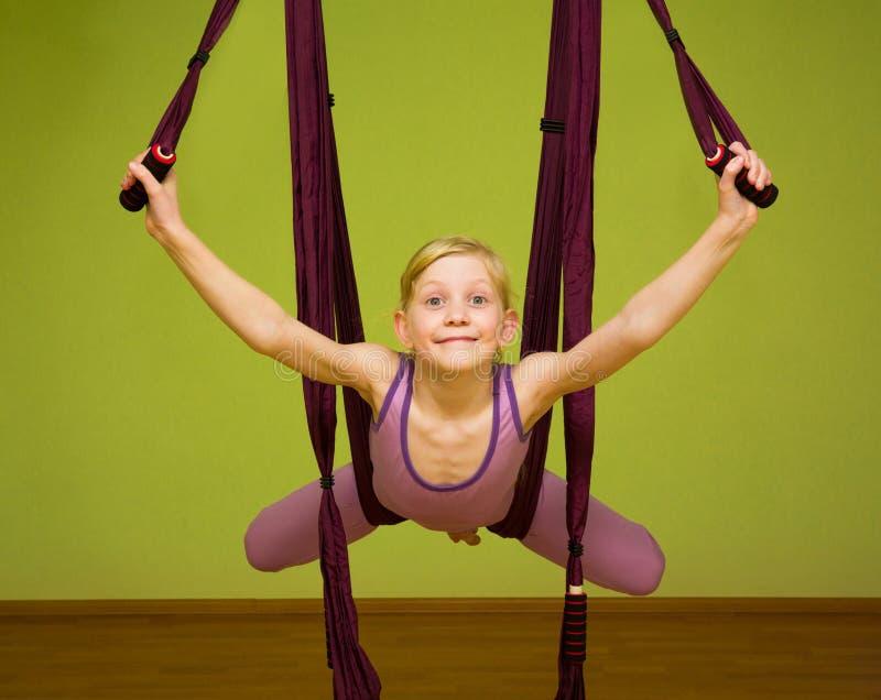 Menina que faz os exercícios aéreos da ioga, internos fotografia de stock royalty free