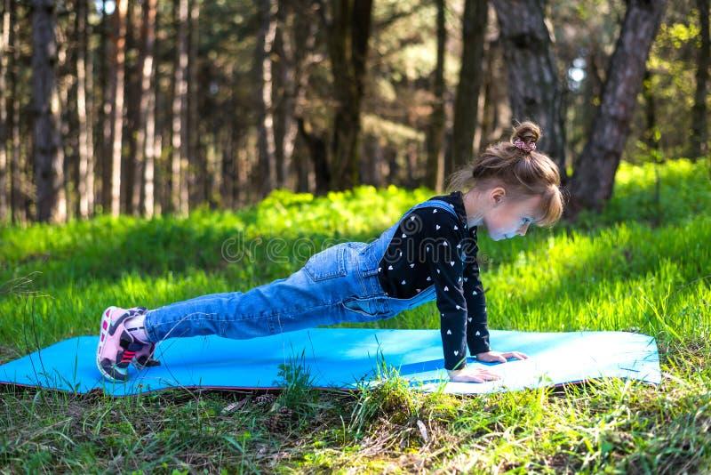 Menina que faz a prancha do exercício, fora imagens de stock royalty free