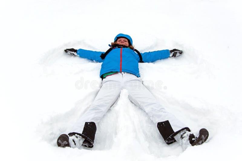 Menina que faz um anjo da neve do inverno fotos de stock