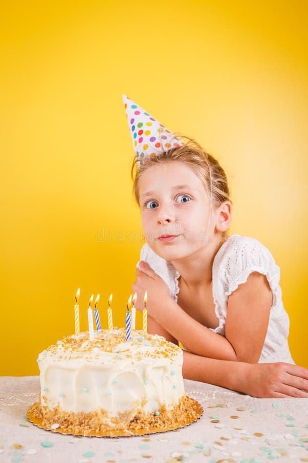 Menina que faz um desejo pelo bolo de aniversário Celebração da festa de anos foto de stock royalty free