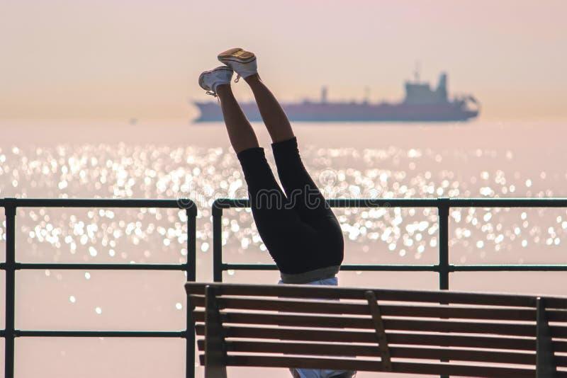 Menina que faz uma prancha no exercício na parte dianteira do mar imagem de stock royalty free