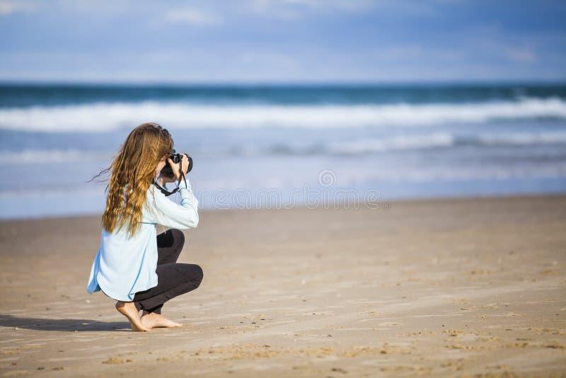 Menina que fotografa o mar foto de stock