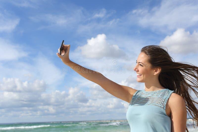 Menina que fotografa um selfie com um telefone esperto na praia imagem de stock royalty free