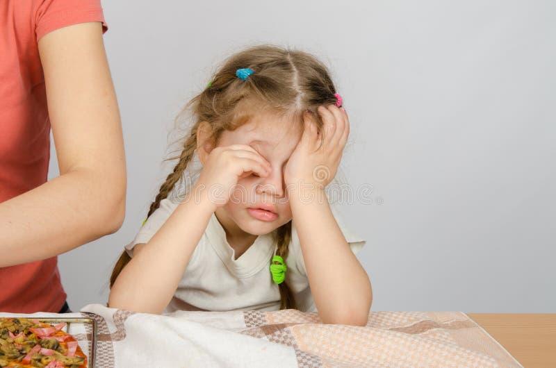 Menina que fricciona cansadamente seus olhos na mesa de cozinha quando a mamã cozinhar imagem de stock royalty free