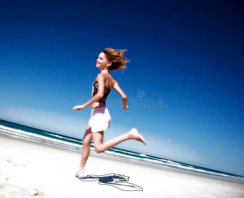 Menina que funciona abaixo da praia imagens de stock