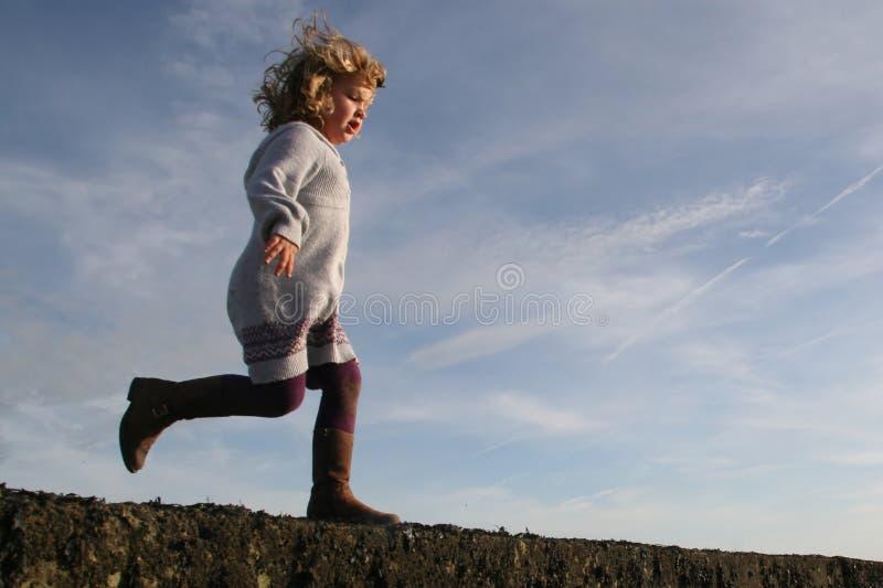 Menina que funciona aproximadamente para saltar foto de stock
