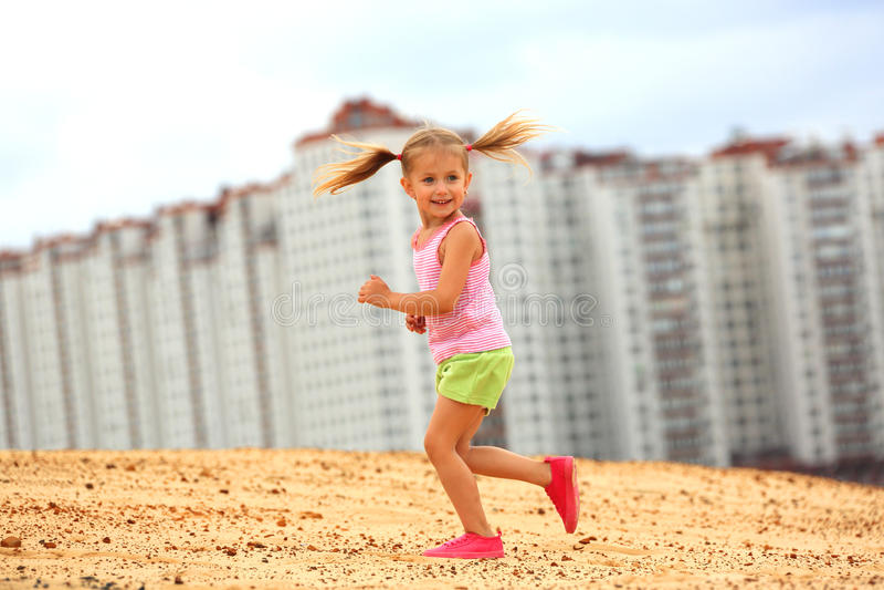 Menina que funciona na areia foto de stock royalty free