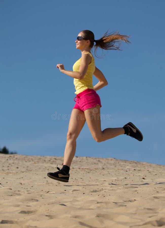 Menina que funciona na areia imagem de stock