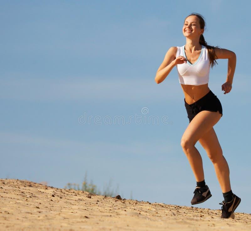 Menina que funciona na areia foto de stock