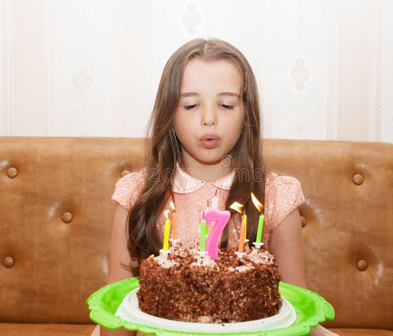 Menina que funde para fora as velas em um bolo de aniversário imagem de stock