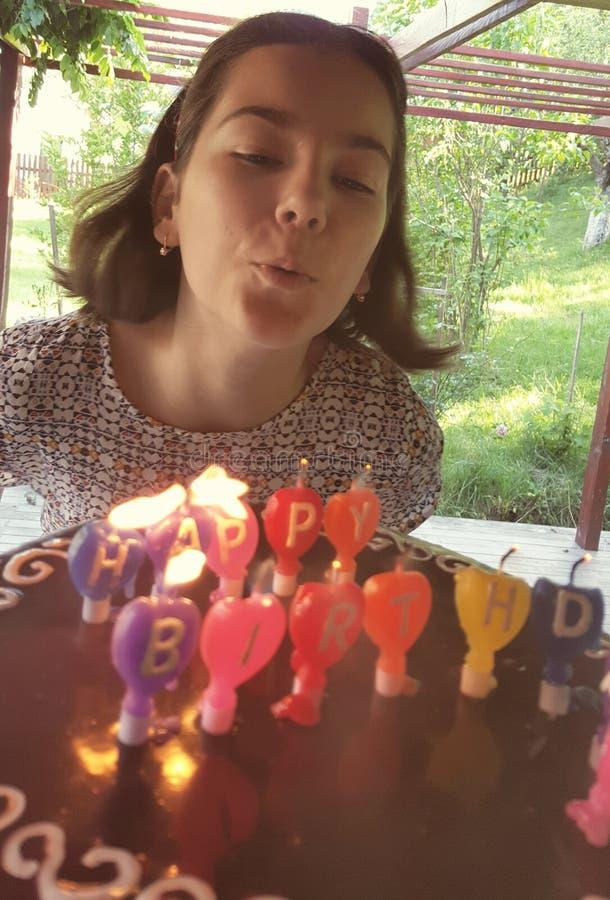 Menina que funde para fora velas do aniversário imagens de stock