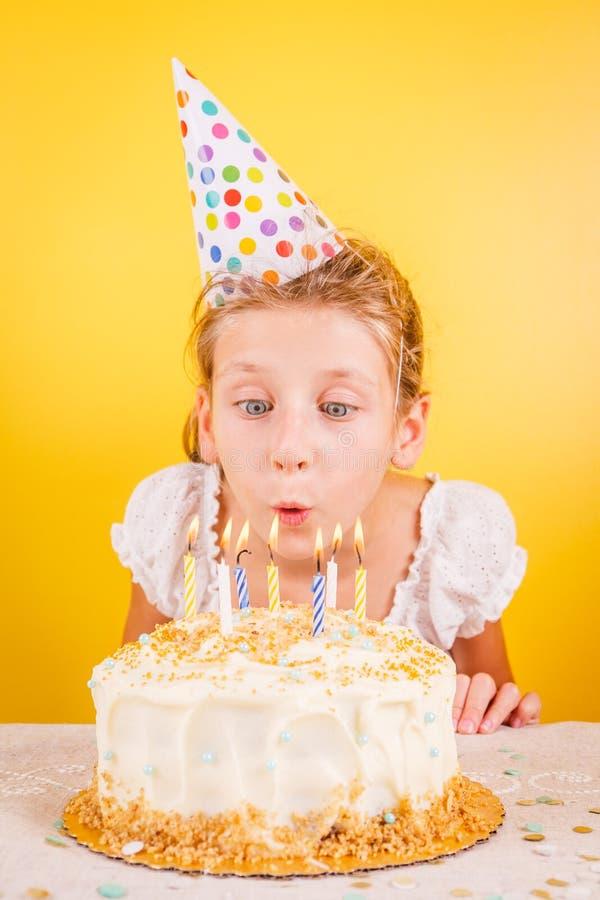 Menina que funde para fora velas no bolo de aniversário Celebr da festa de anos foto de stock