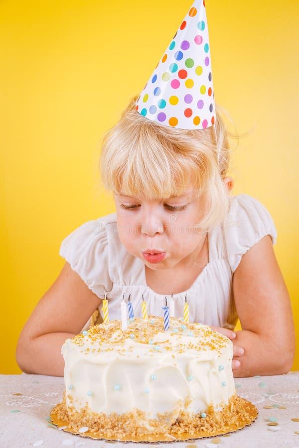 Menina que funde para fora velas no bolo de aniversário Celebr da festa de anos fotos de stock