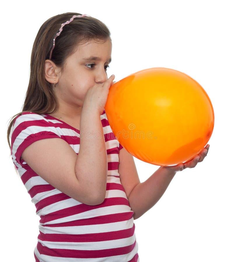 Menina que funde um balão fotografia de stock